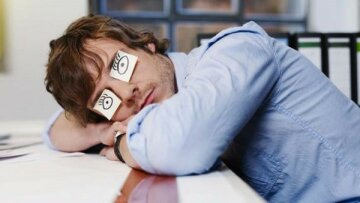 Young Man Sleeping with Drawn on Eyes — Image by © Michael Haegele/Corbis