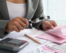 Businesswoman checking bills using magnifying glass