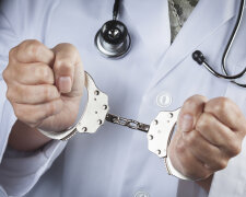 Female Doctor or Nurse In Handcuffs Wearing Lab Coat and Stethoscope.