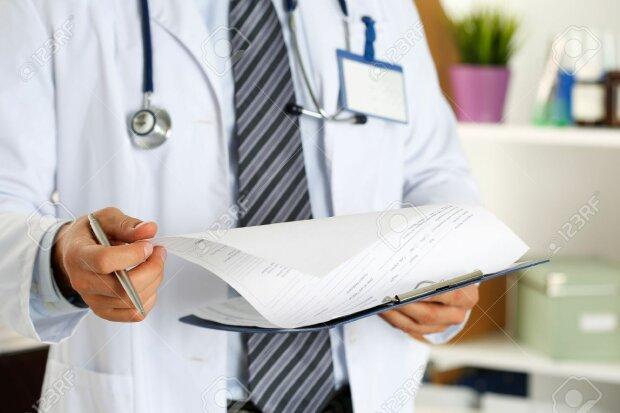 56354604-homme-docteur-en-médecine-main-tenant-un-stylo-en-argent-à-la-recherche-en-gros-plan-presse