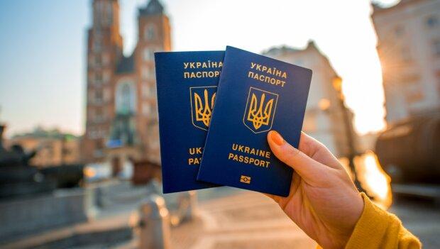 Female hands holding Ukrainian abroad passports on the Krakow city center background