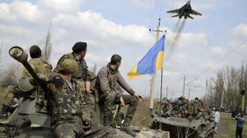 Ukrainian servicemen look at a Ukrainian military jet fly above them in Kramatorsk