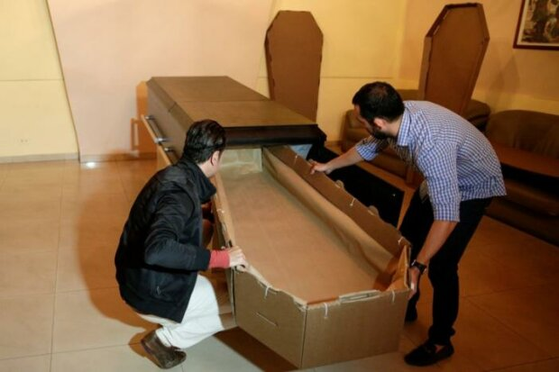 Elio Angulo and Alejandro Blanchard put a cardboard coffin inside a crate at a mortuary in Valencia