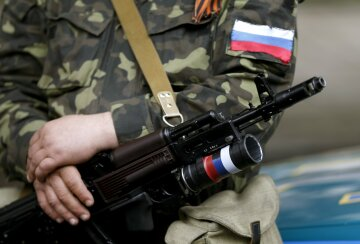 Armed pro-Russian activist holds his weapon as he stands near the seized regional government headqua