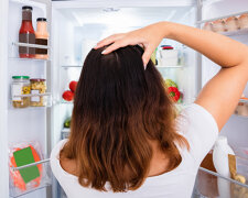 Confused Woman Searching For Food In The Fridge