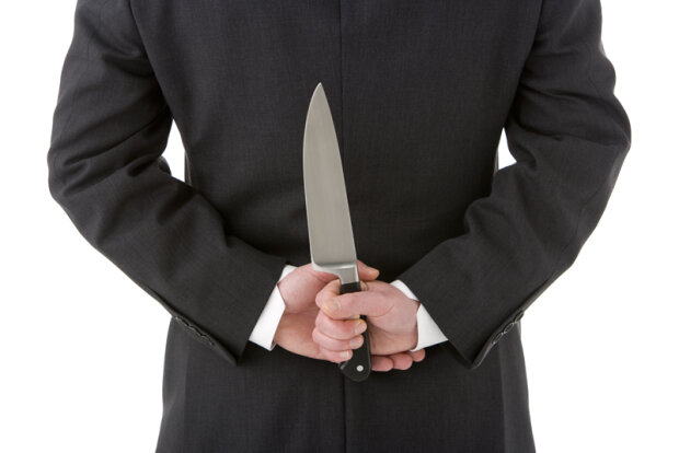 Businessman Holding Knife Behind His Back
