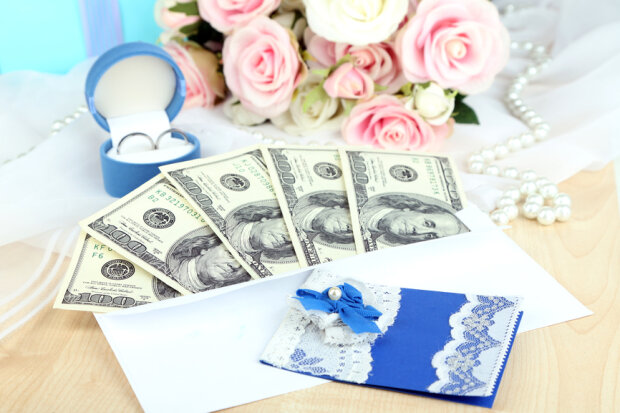 Dollar bills in envelope as gift at wedding on wooden table close-up