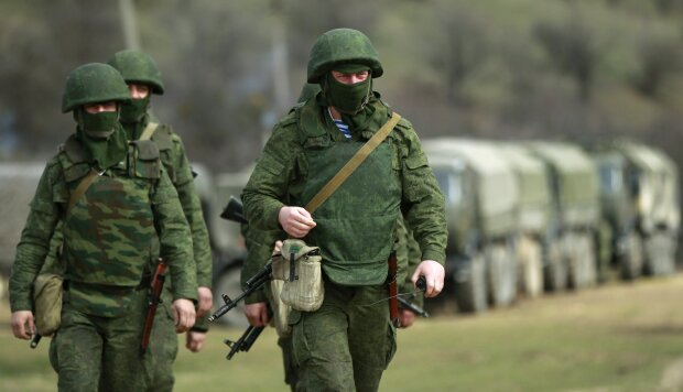 Armed men, believed to be Russian servicemen, march outside Ukrainian military base in Perevalnoye