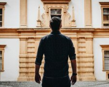 a_man_in_shadow_stands_with_his_back_toward_the_camera__facing_an_ornate_building_facade