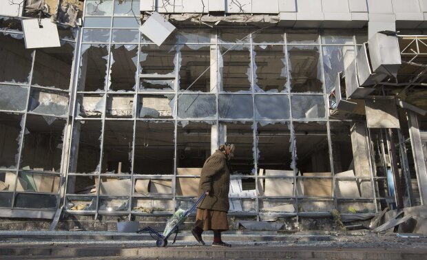 A woman pulls her shopping trolley as she walks past a building that was damaged by shelling in Done