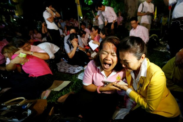 People weep after an announcement that Thailand's King Bhumibol Adulyadej has died, at the Sir