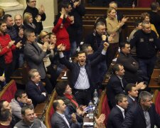 Ukrainian opposition members celebrate during the voting in parliament in Kiev