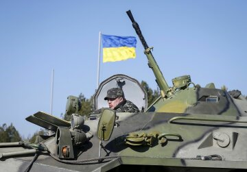 A Ukrainian soldier rides on an armoured personnel carrier during a military exercise near the villa