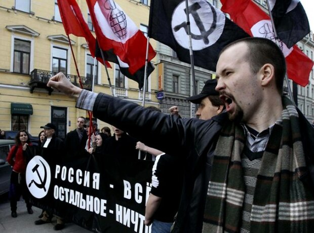 Supporters of the banned National Bolshevik party shout slogans standing with a poster reading &#821