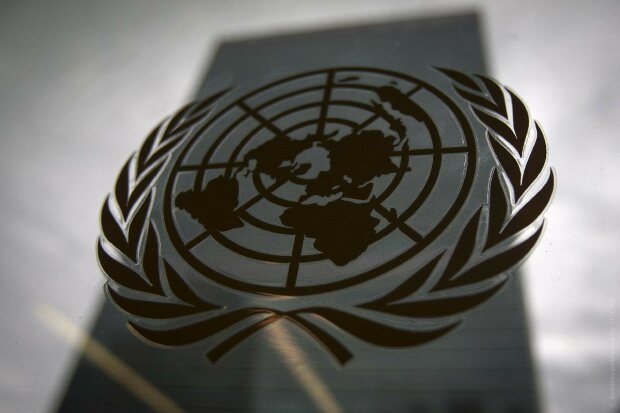 The United Nations headquarters building is pictured though a window with the UN logo in the foregro